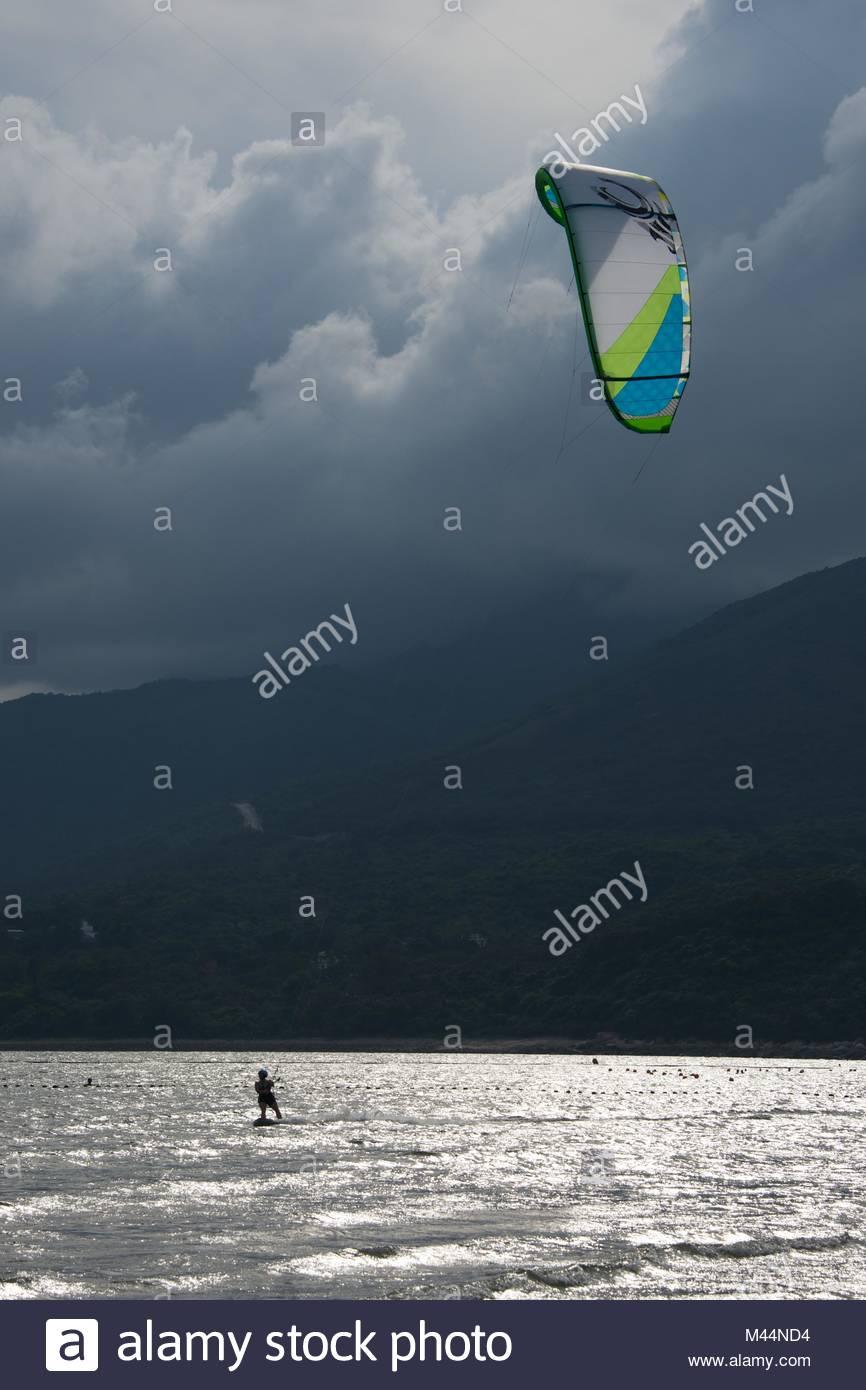 Kite surfer retroiluminada contra un cielo amenazador Imagen De Stock