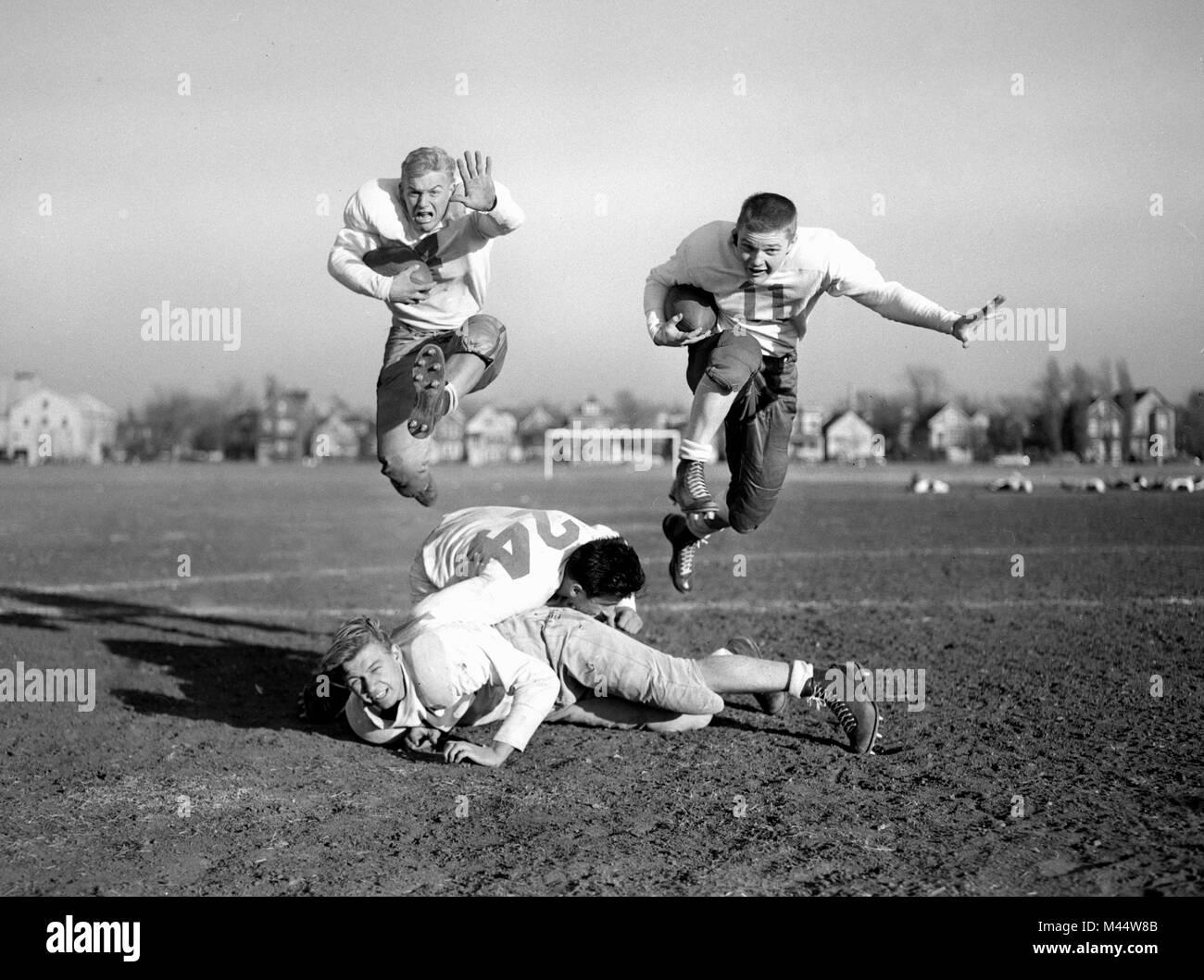 Dos futbolistas adolescentes sin cascos saltan sobre sus compañeros, replicando la acción del juego durante la práctica, ca. 1950. Foto de stock