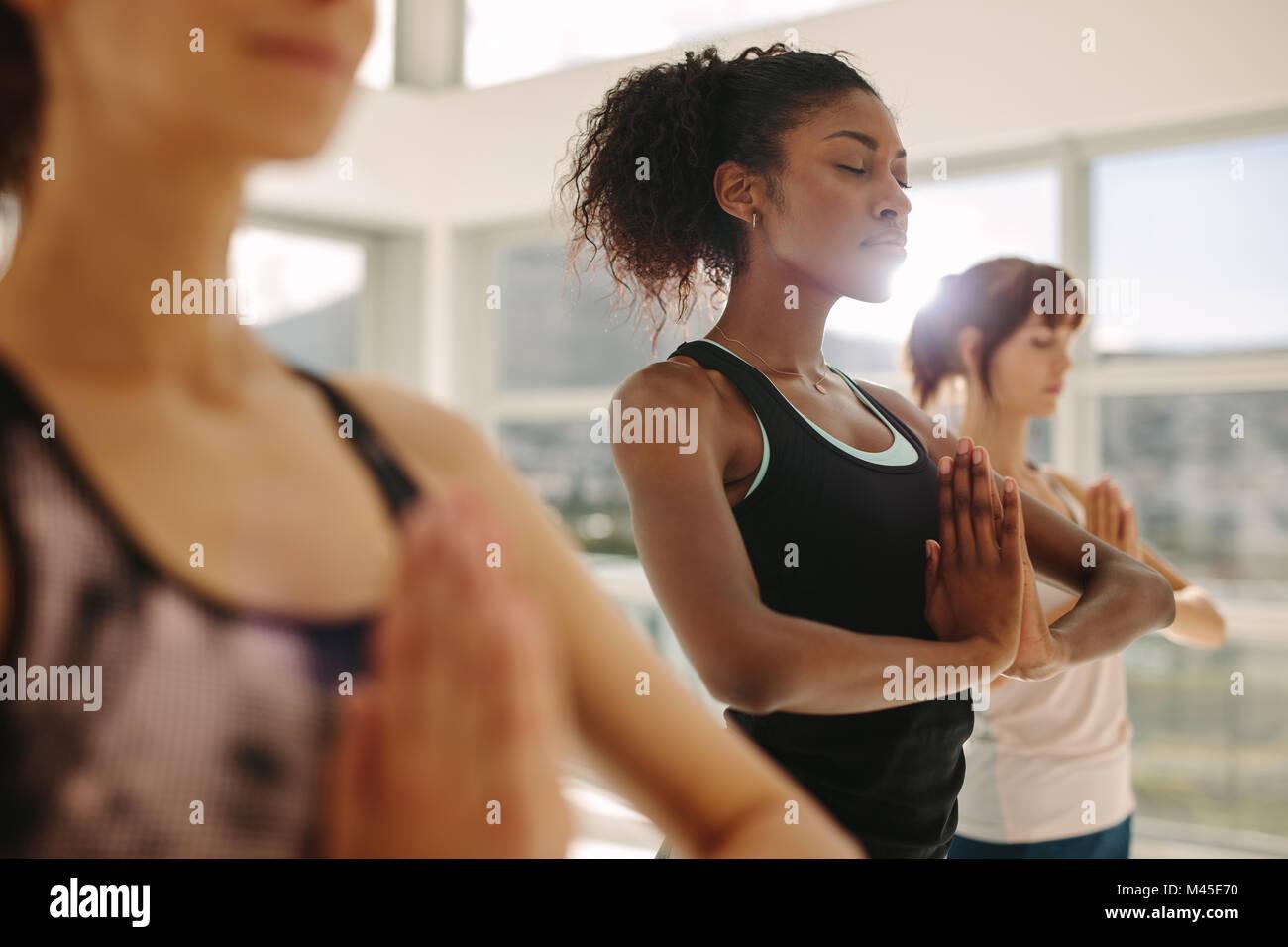 Colocar joven practicar yoga con amigos. Mujeres haciendo gimnasia yoga meditación interior en la clase de Imagen De Stock