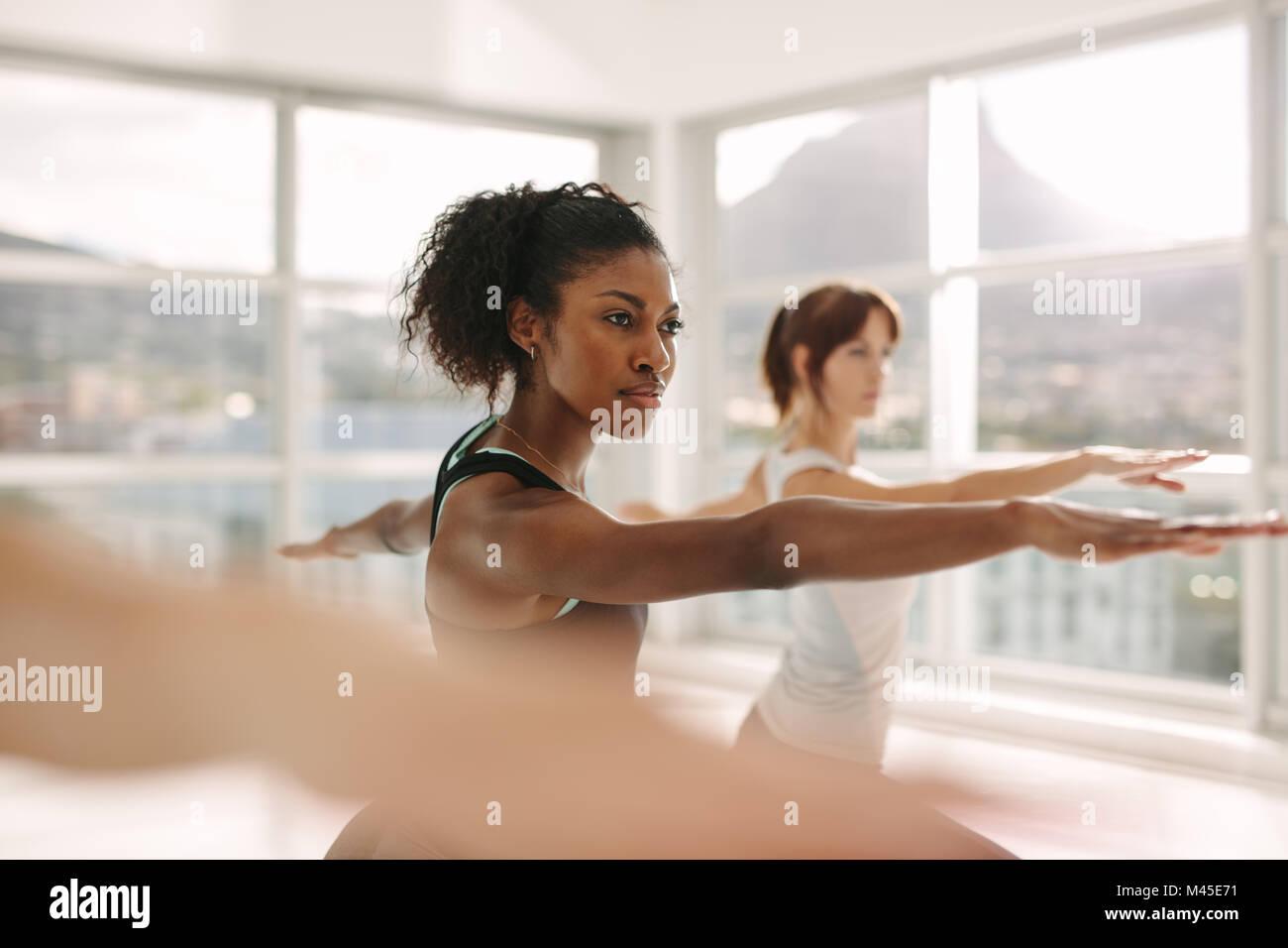 Las mujeres que realizan ejercicios de estiramiento y yoga entrenar en el gimnasio. Entrenador femenino con su estudiante Imagen De Stock