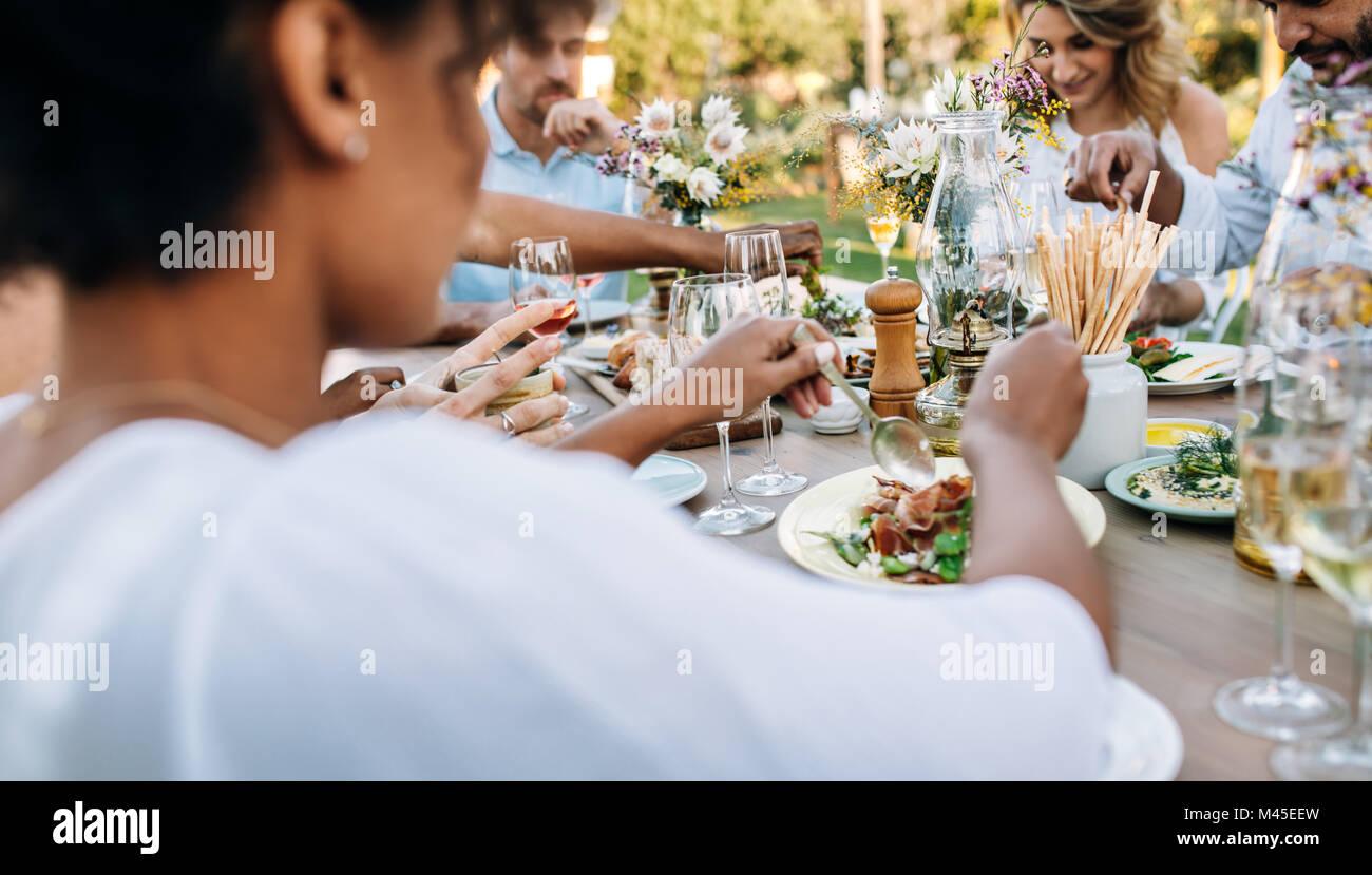 Grupo de amigos disfrutando de comida en la fiesta al aire libre. Hombres y mujeres almorzando juntos en un restaurante. Imagen De Stock