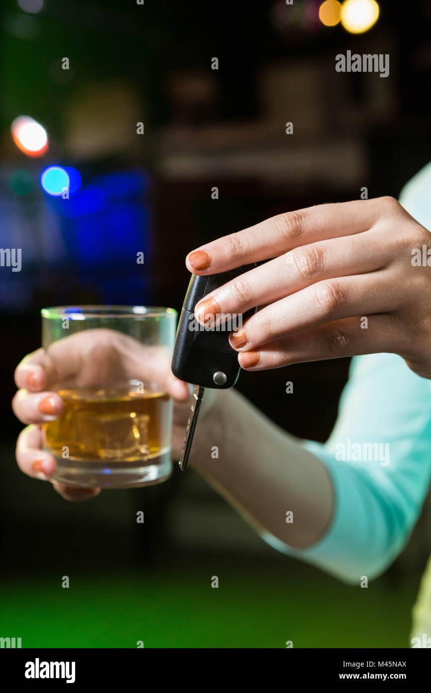 Mujer sosteniendo un vaso de whisky y las llaves del coche Foto de stock