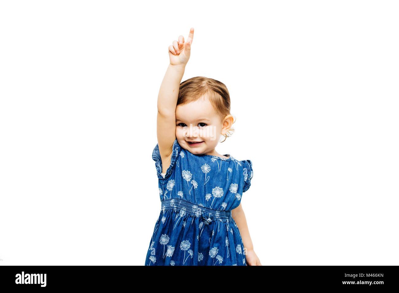 Niño Niña levantando la mano con el dedo índice apuntando hacia arriba Imagen De Stock