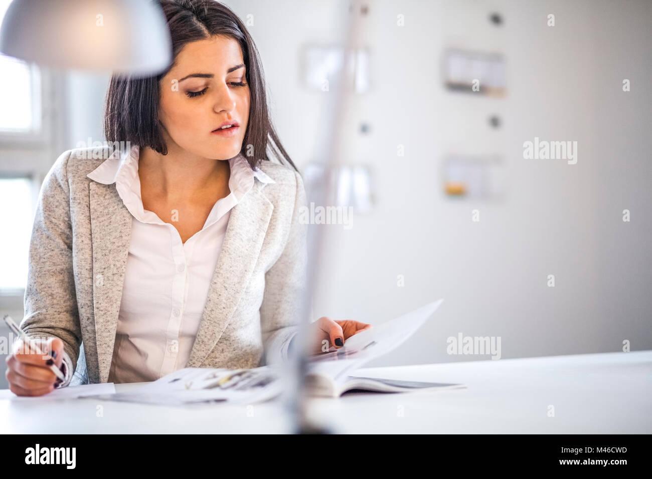 La empresaria leyendo folleto mientras toma notas en la oficina Imagen De Stock