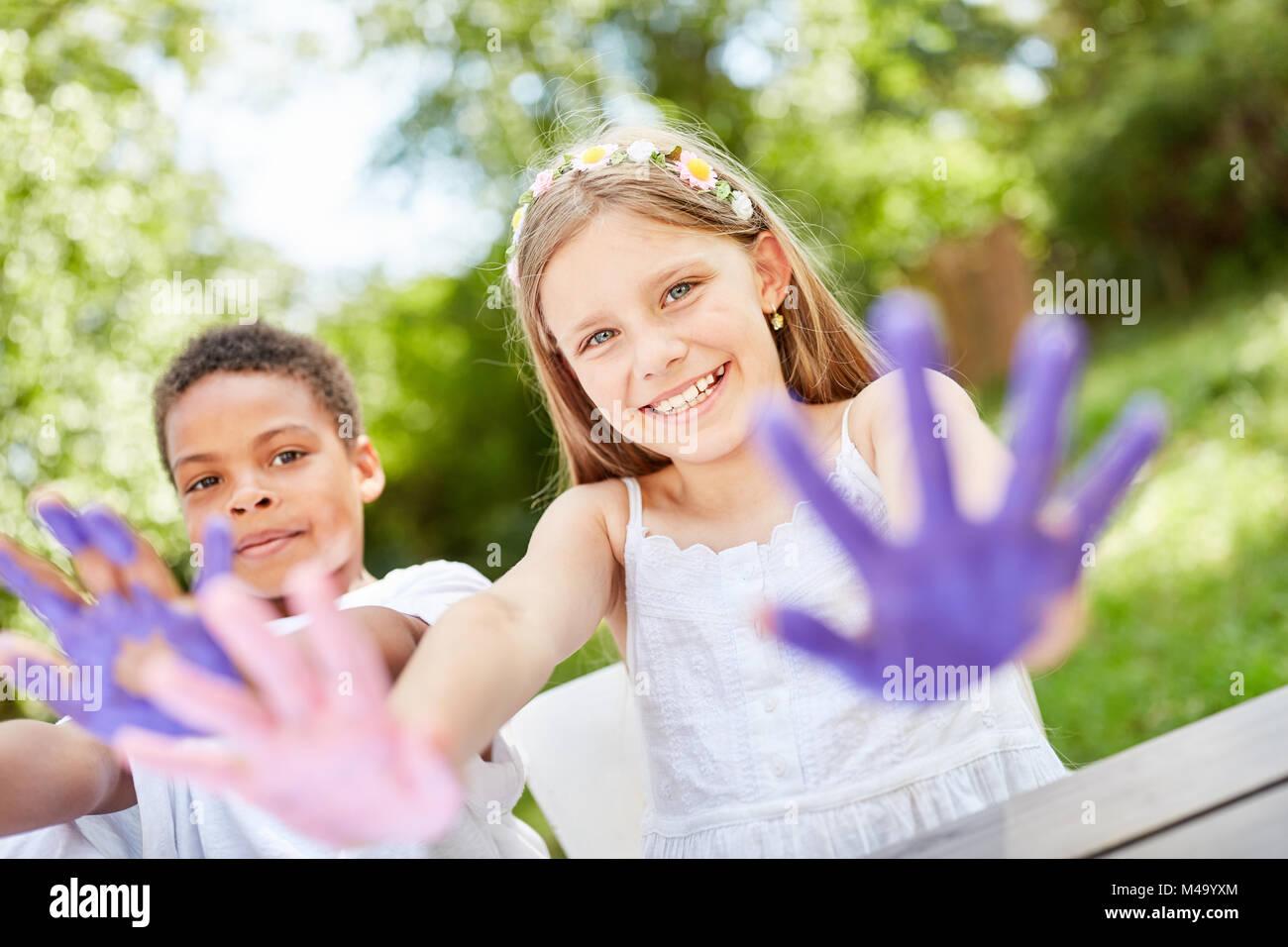 Los niños juegan y pintar con pinturas de dedos en la fiesta de cumpleaños en el jardín Imagen De Stock
