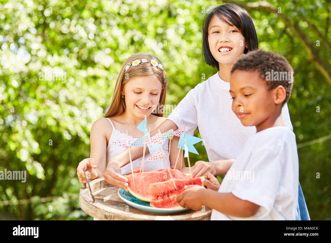 Grupo Multicultural de niños distribuye una sandía en garden party Imagen De Stock