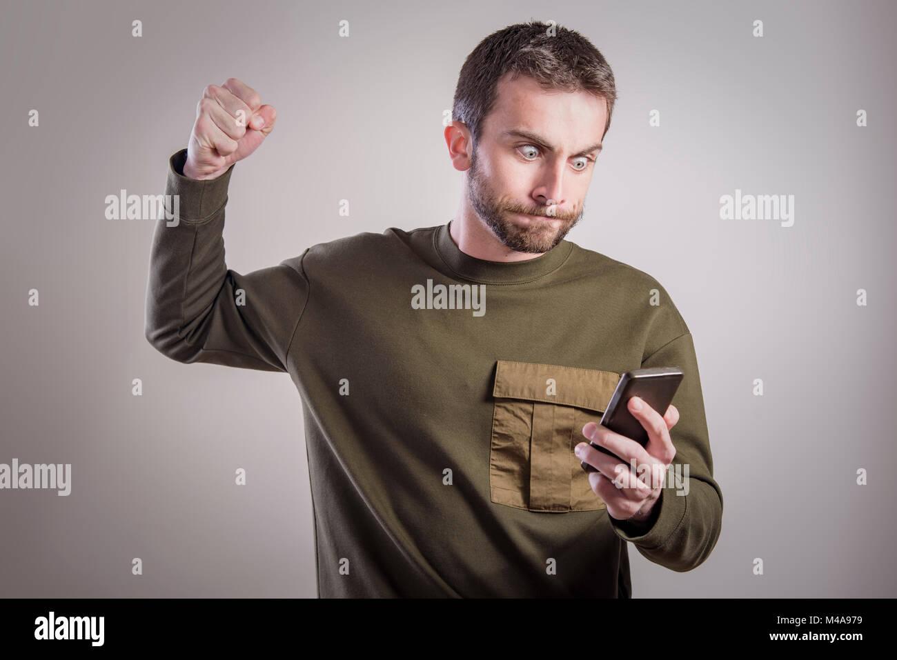 El hombre enojado con su teléfono, indignado y enfurecido Imagen De Stock
