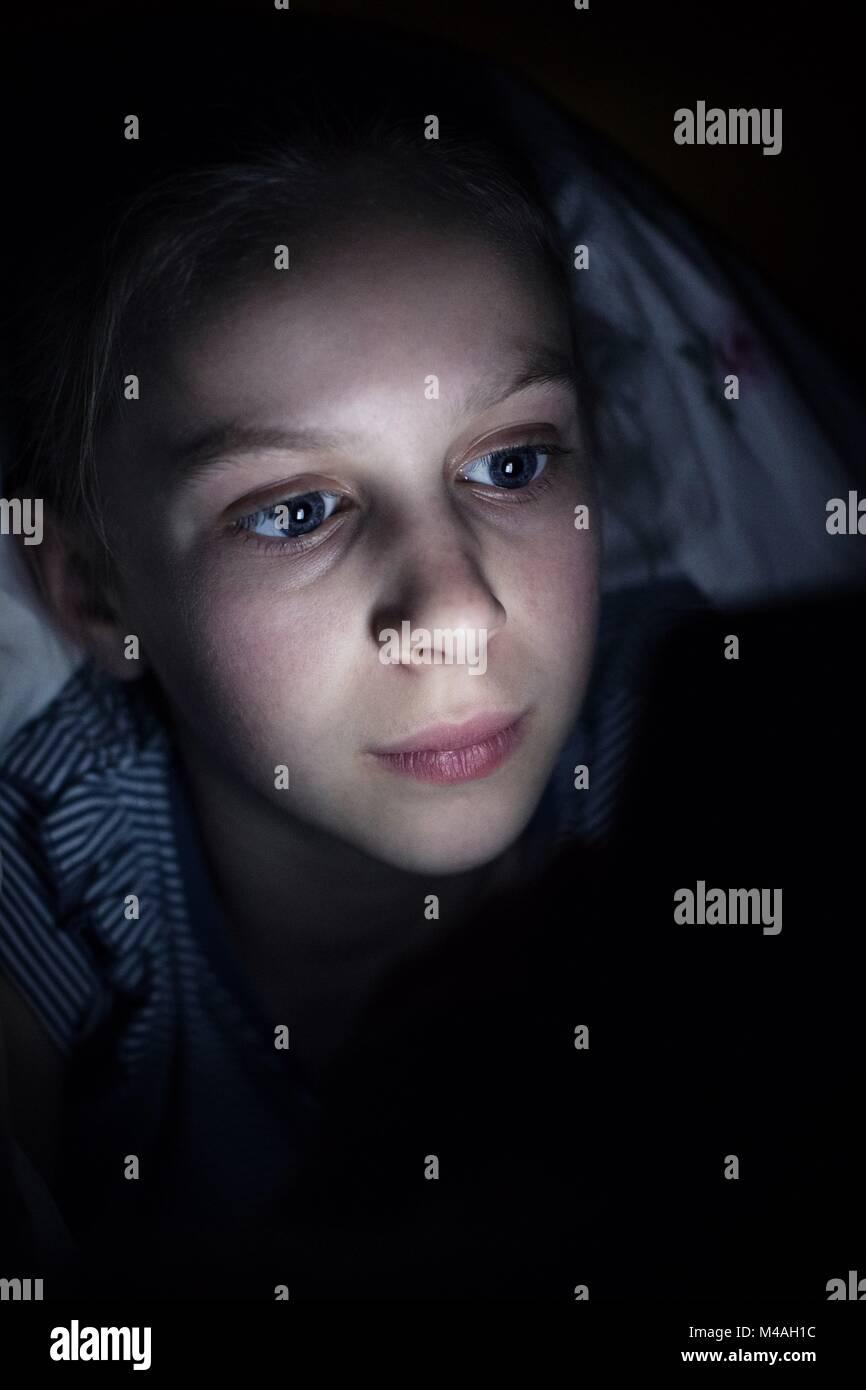Chica utilizando el teléfono móvil oculto bajo el edredón de la cama en la noche Imagen De Stock