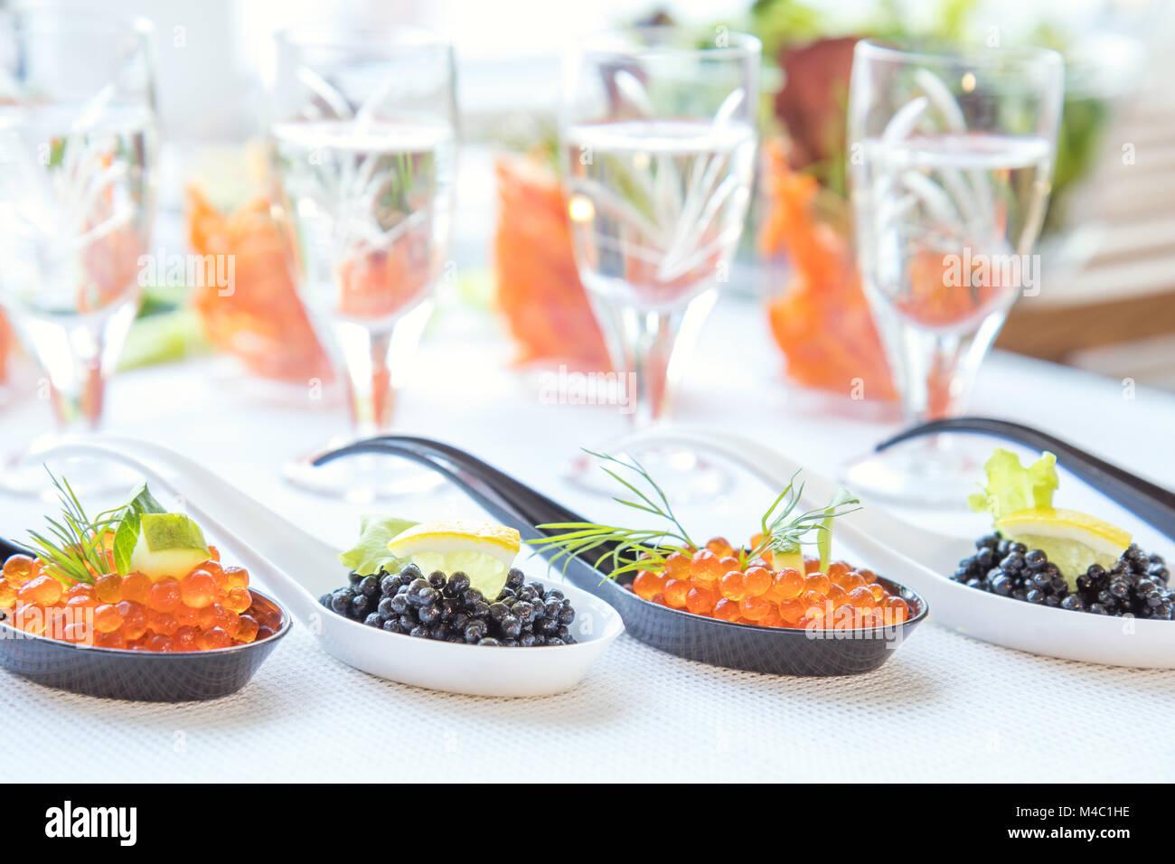 Caviar rojo y negro pescado en blanco, negro cucharas Imagen De Stock