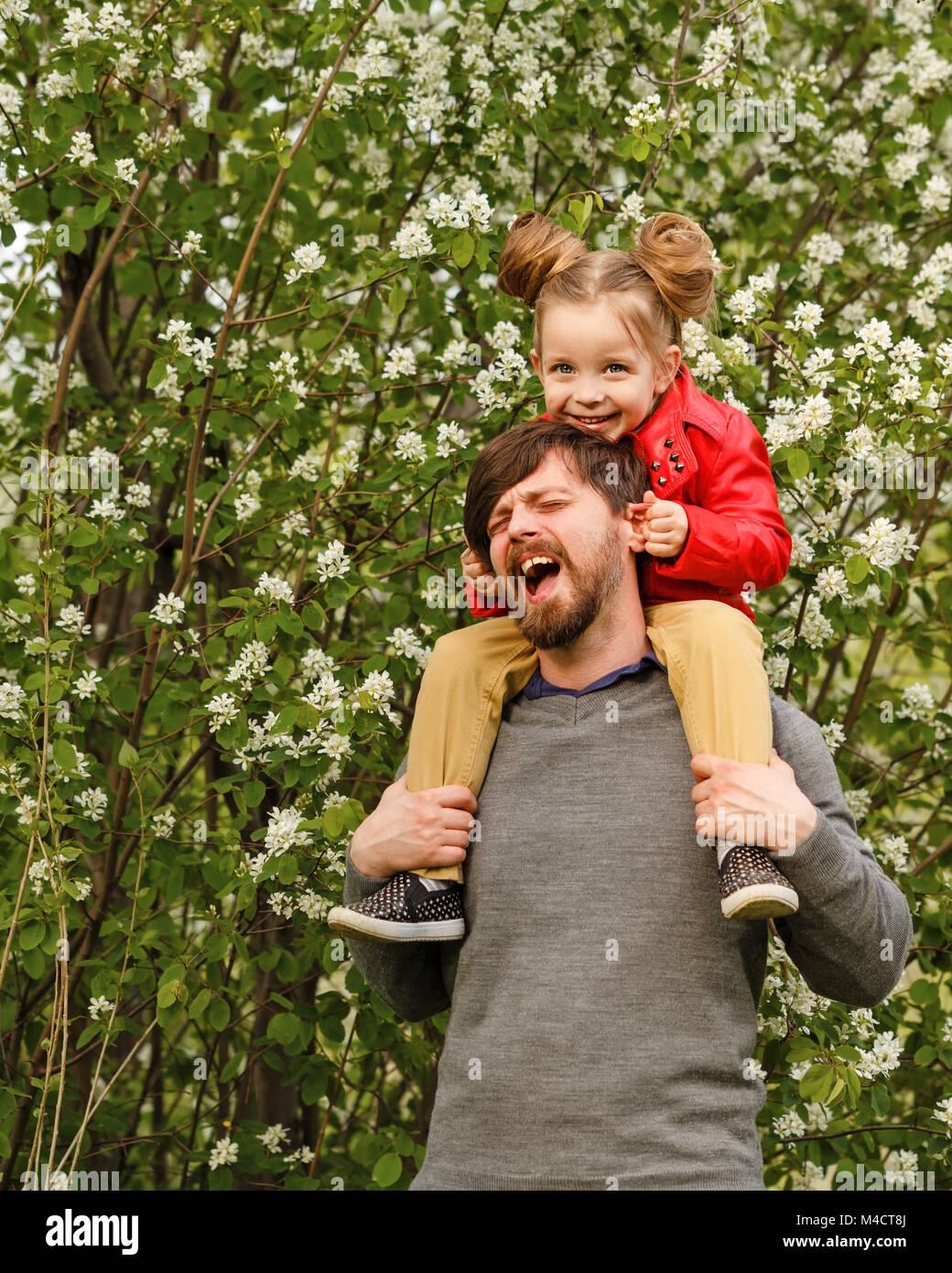 El tiempo de la familia. El padre tiene sobre sus hombros una pequeña hija en una chaqueta de cuero. Piggyback. Imagen De Stock