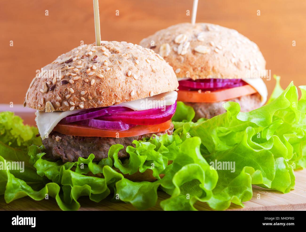 Hamburguesa con ensalada, cebolla, tomate y pan fresco Foto de stock