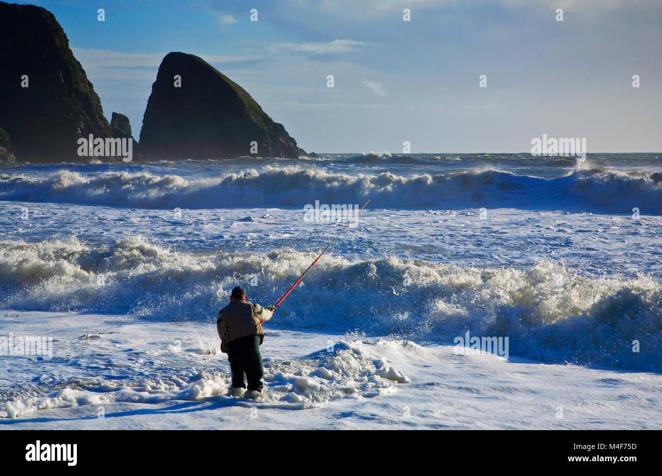 La pesca marina con caña de Bass en Ballydowane Playa, Costa del cobre, el condado de Waterford, Irlanda Imagen De Stock