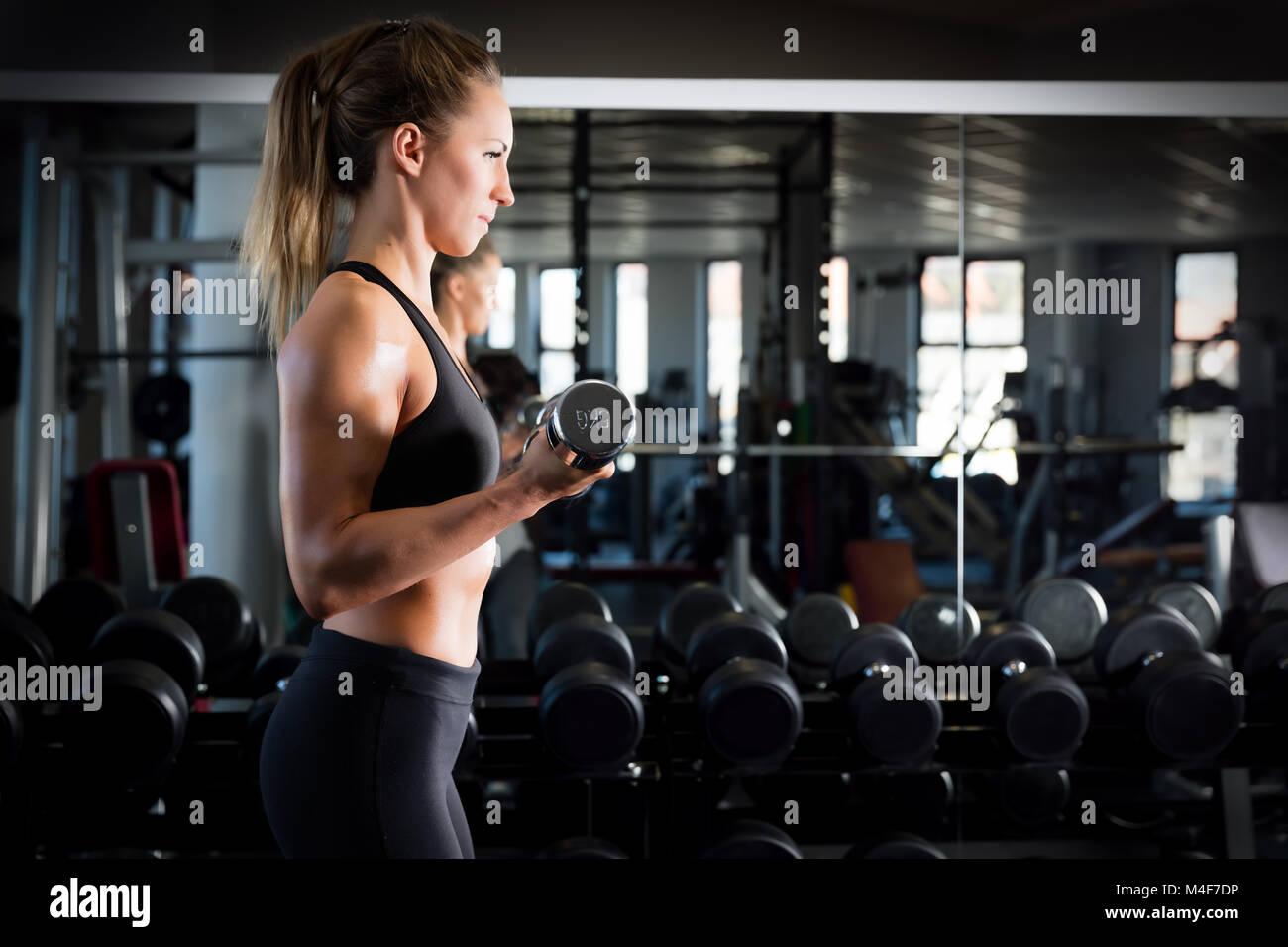 Mujer atractiva de levantamiento de pesas en el gimnasio. Imagen De Stock