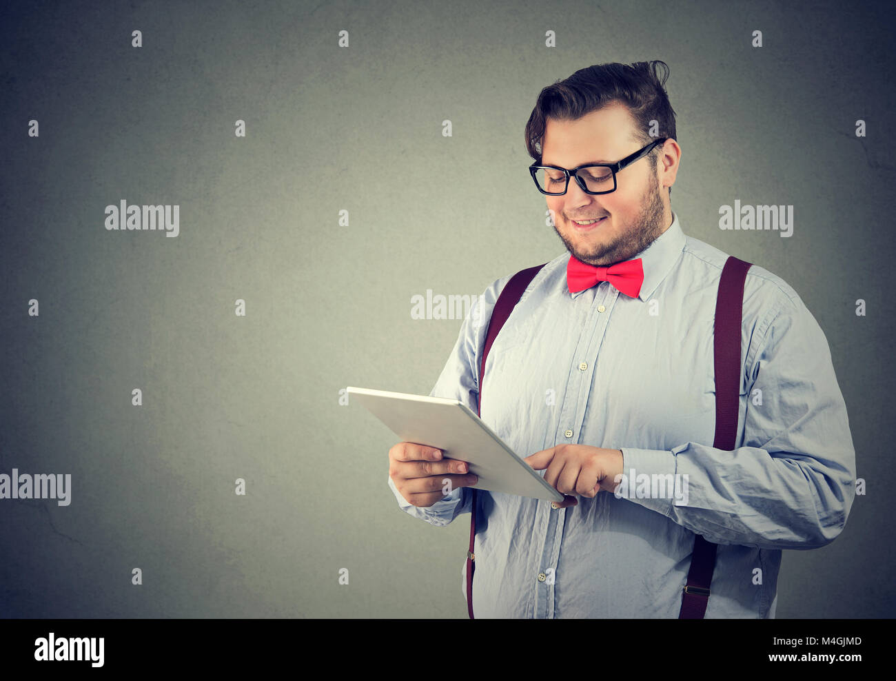 Impertinente joven hombre de anteojos mirando feliz mientras tocas tablet posando sobre fondo gris. Imagen De Stock