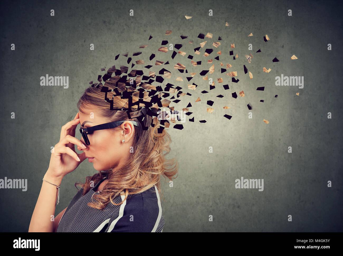 La pérdida de memoria debido a la demencia o daño cerebral. El perfil lateral de una mujer perdiendo partes Imagen De Stock