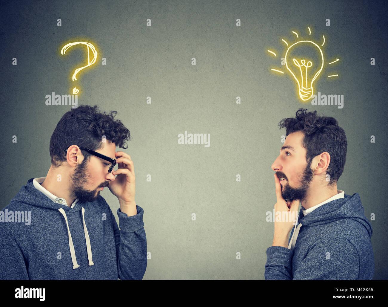 Dos hombres pensando uno tiene una pregunta otra solución con bombilla sobre la cabeza aislado sobre fondo Imagen De Stock