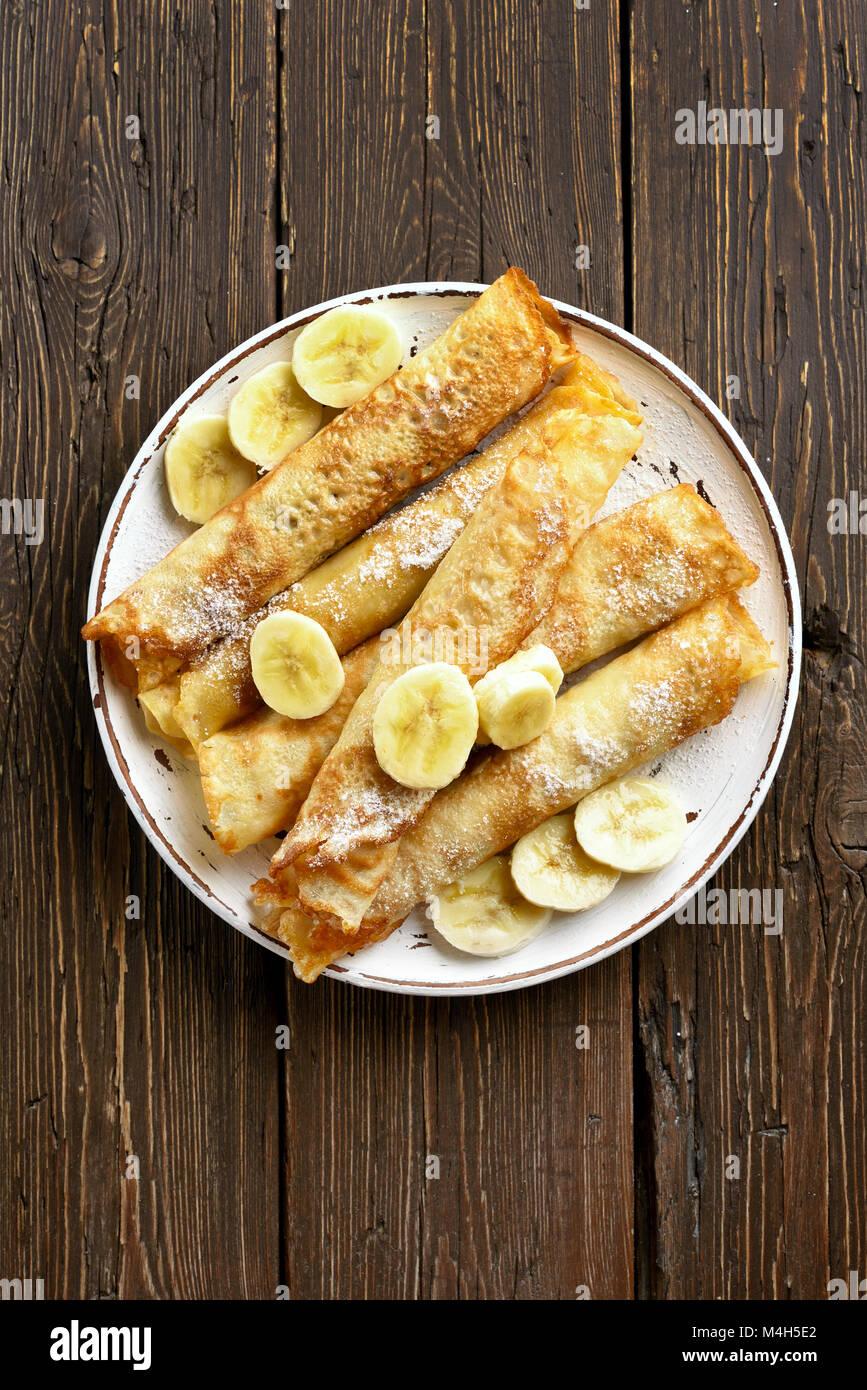 Los pancakes, crepes rollo con rodajas de plátano sobre fondo de madera con espacio de copia. Vista superior, Imagen De Stock