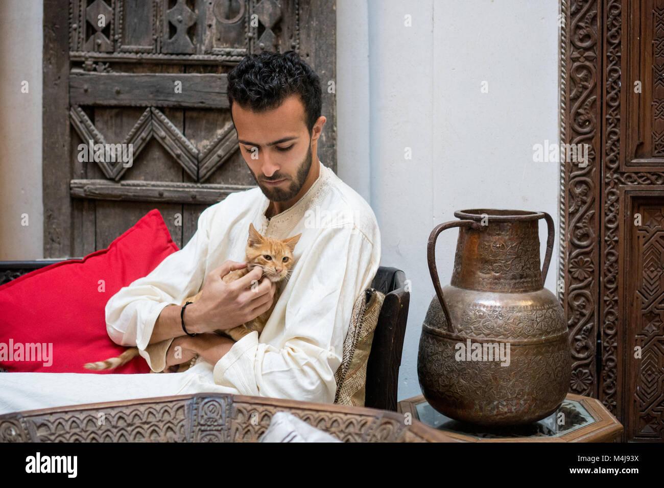 Joven musulmلn en vestimentas tradicionales sosteniendo un gato amarillo delante de un muro decorado Foto de stock