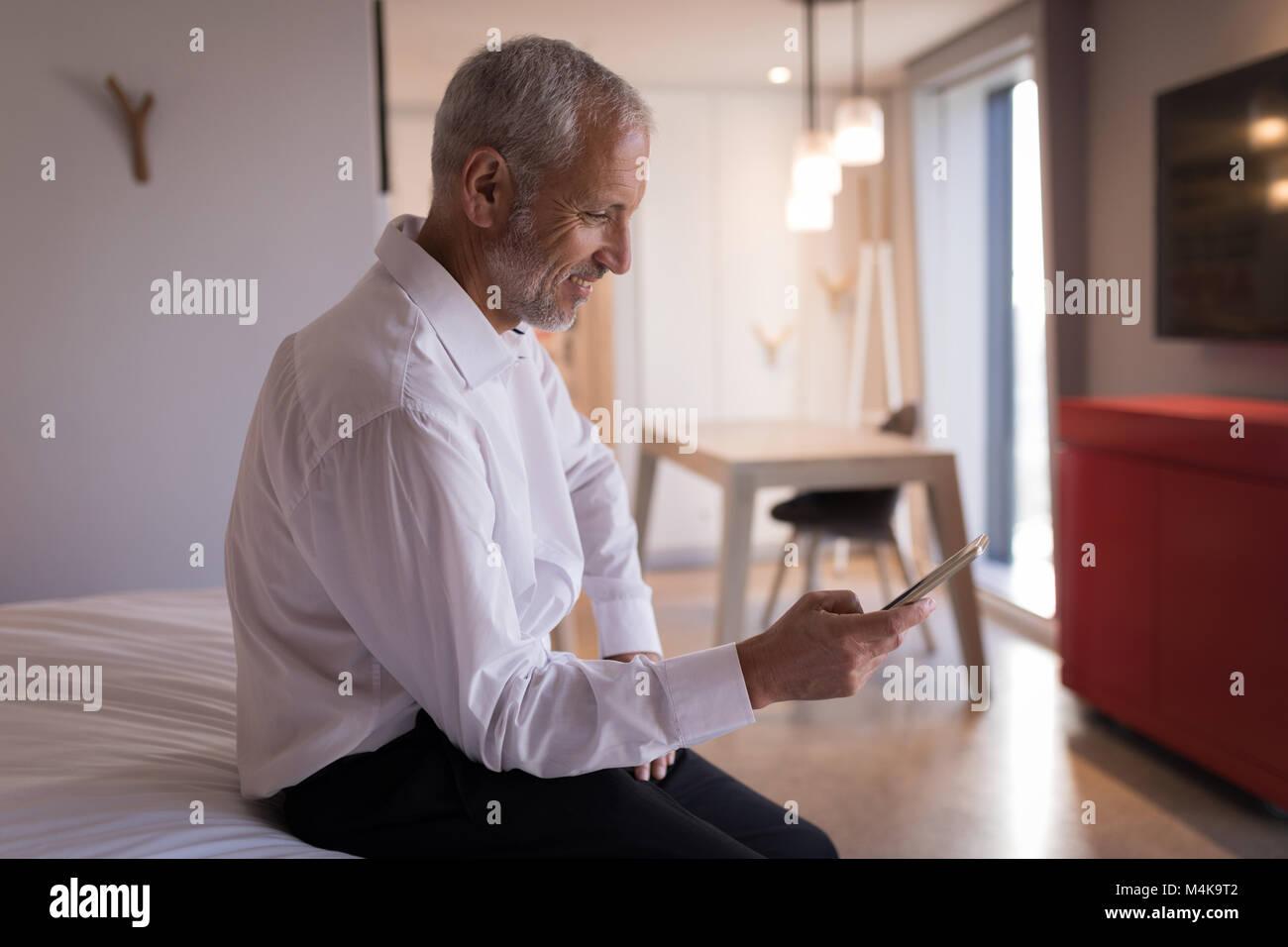 Empresario utilizando un teléfono inteligente en la cama Imagen De Stock