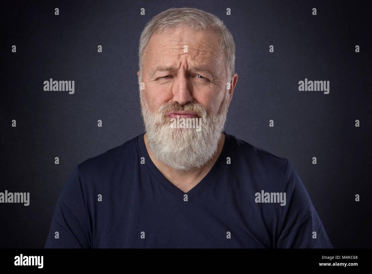 Un hombre de 60 años con barba gris posando estropeó la mueca en el studio Imagen De Stock
