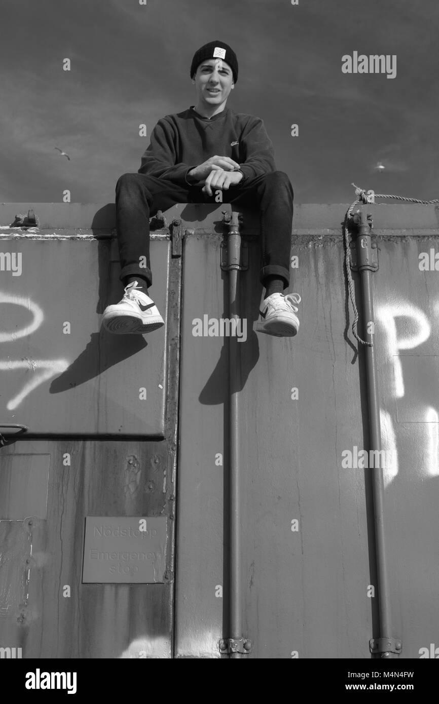 Industrial en blanco y negro retrato de un hombre joven en la cima de un viejo contenedor marítimo en Cruden Bay Harbor, aberdeenshire, Escocia, Reino Unido. Invierno, 2018. Foto de stock