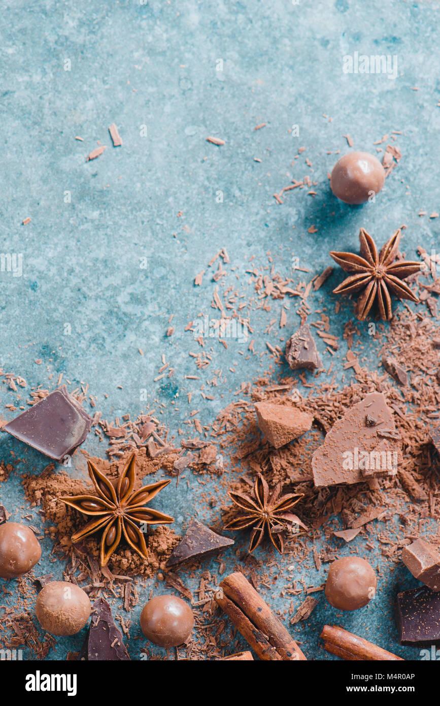 Postre ingredientes laicos plana. Porciones de leche y chocolate amargo, especias y cacao dispersas sobre un fondo Foto de stock