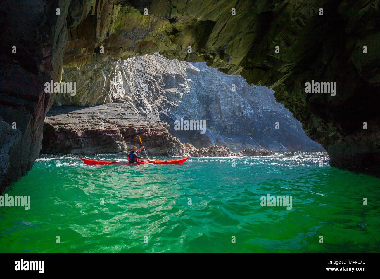 Mar kayakista explorar una cueva cerca de Glencolmcille, Condado de Donegal, Irlanda. Foto de stock