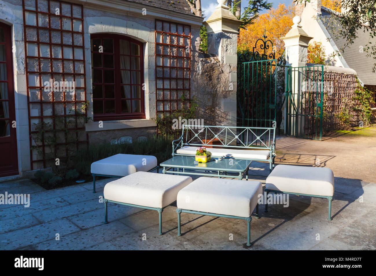Muebles de exterior, banquetas y sofás están alrededor de una mesa ...