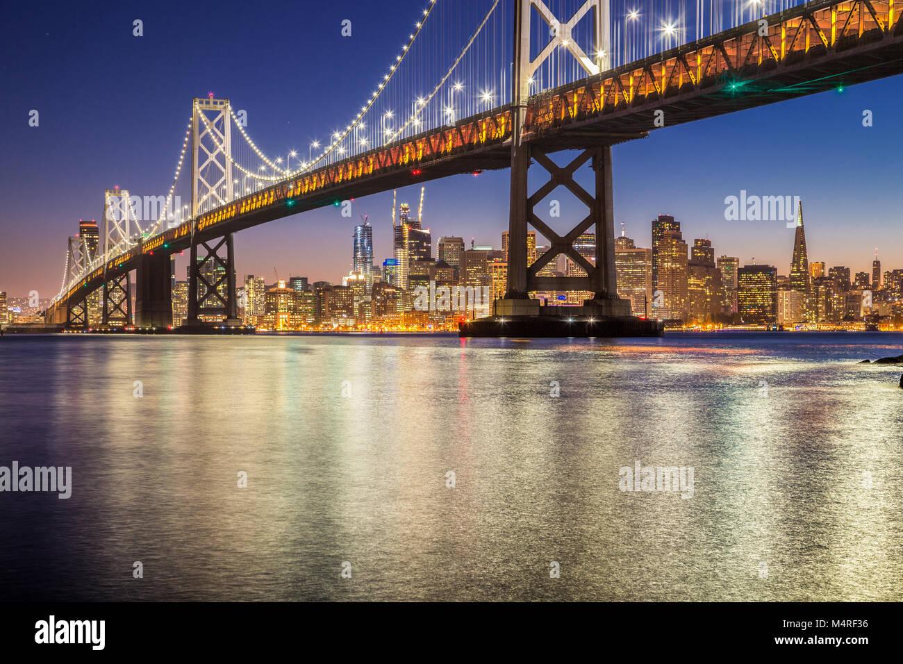 Classic vista panorámica del famoso Puente de la Bahía de Oakland con el horizonte de San Francisco iluminado Imagen De Stock