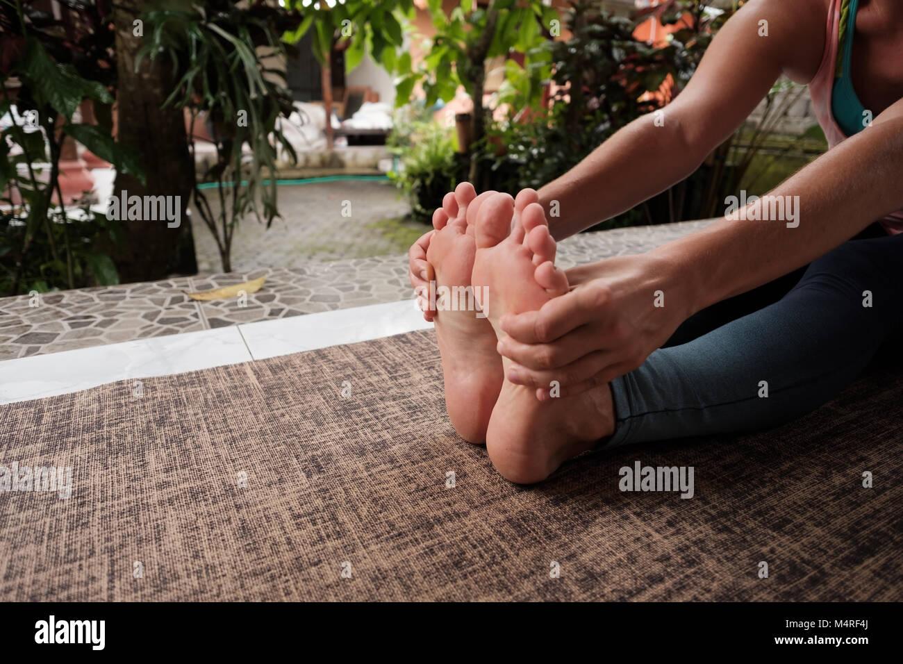 Detalle de la mujer caucásica haciendo ejercicios de yoga asana. Chica sentado adelante doblar pose. Estilo Imagen De Stock