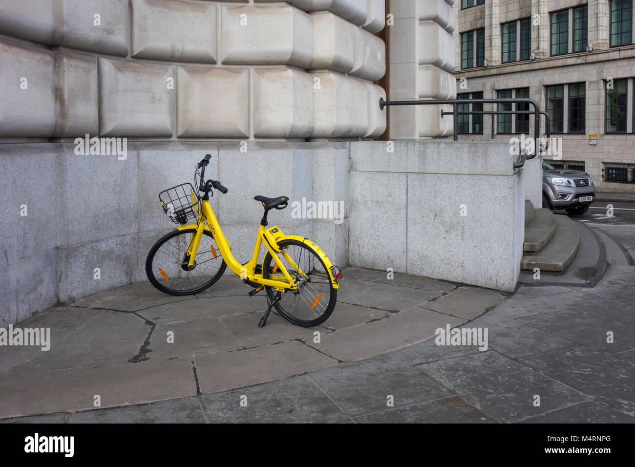 Amarillo Ofo alquilar moto estacionada fuera de una oficina en Londres, Reino Unido Imagen De Stock