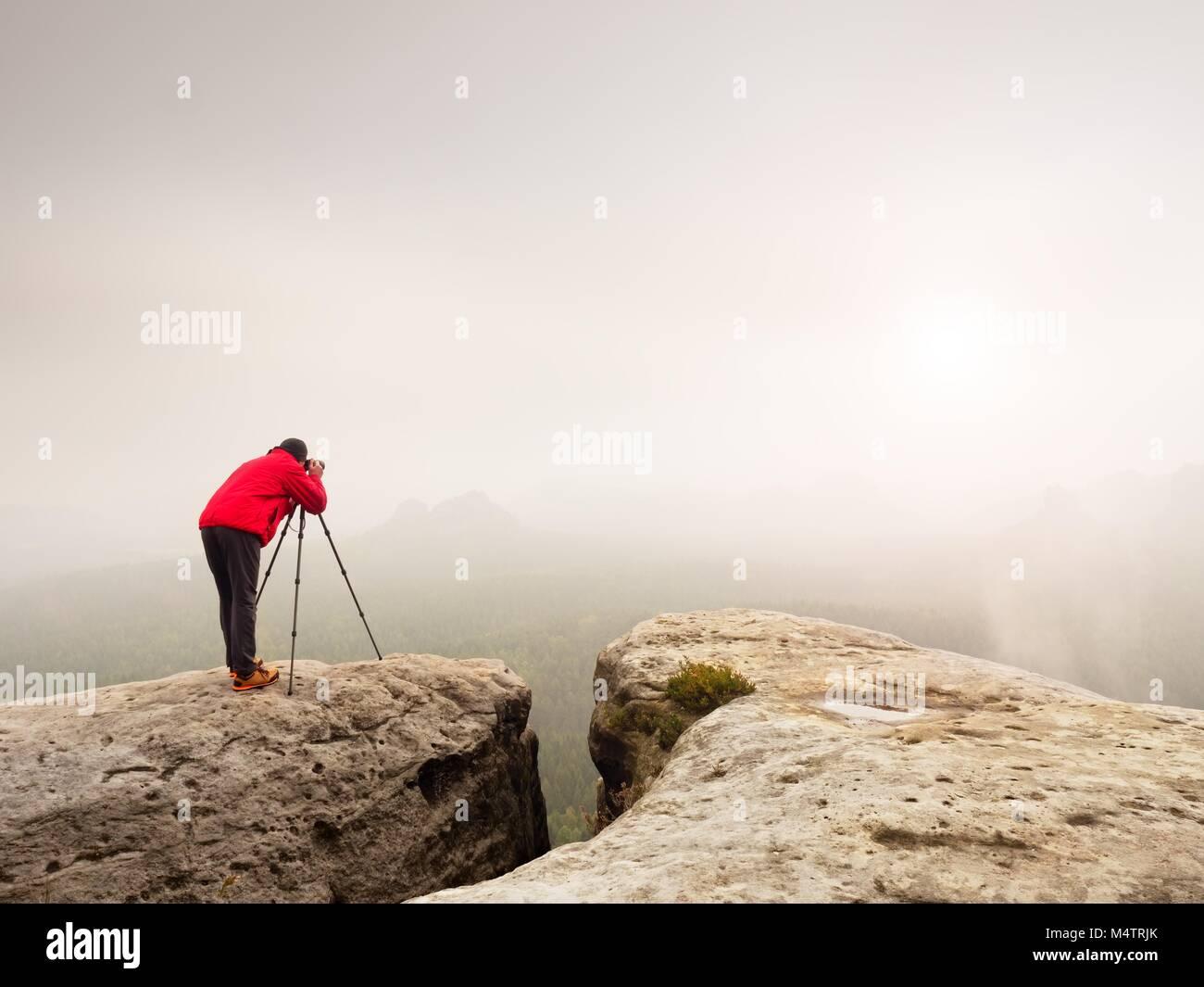 Fotógrafo profesional disparo. Artista permanecer con trípode en la Cumbre y toma fotos de coutryside Imagen De Stock