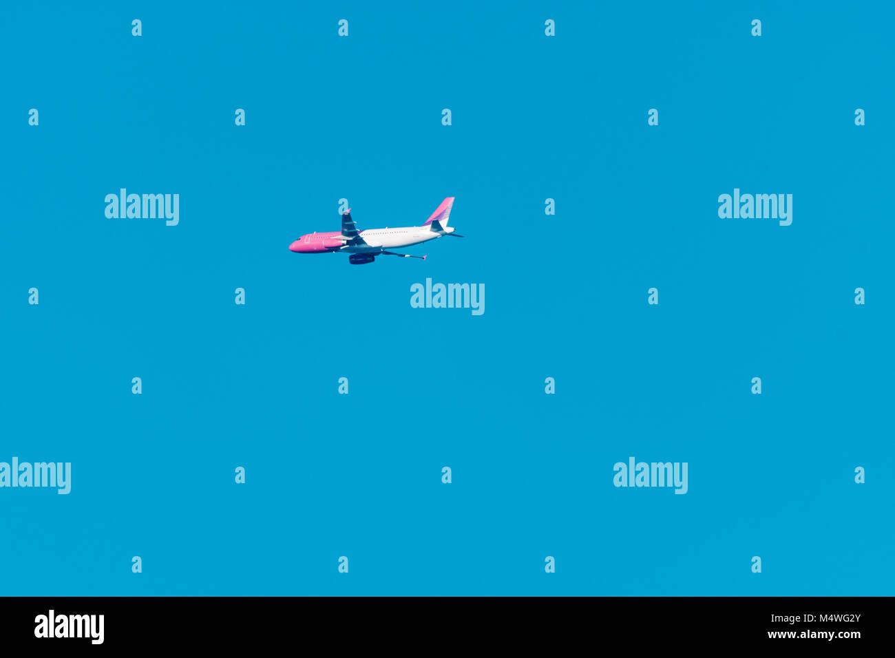 Gran avión de pasajeros en lo alto de un cielo azul claro. Un cielo azul sin nubes. Imagen De Stock