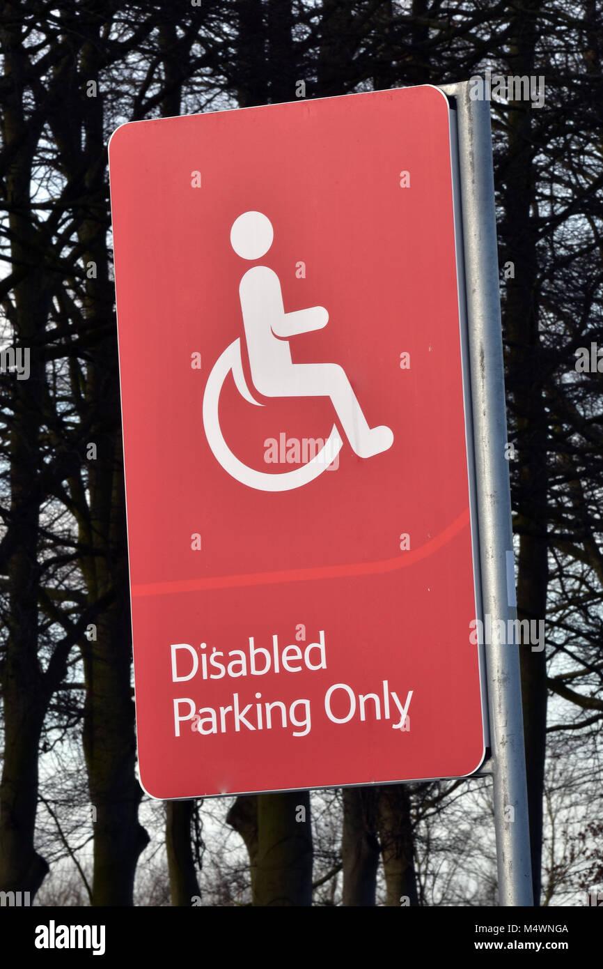 Una roja y muy perceptible conspicuo único signo de estacionamiento de discapacitados en un gran supermercado o hipermercado car park. Espacios para aparcar un coche o vehículo Foto de stock