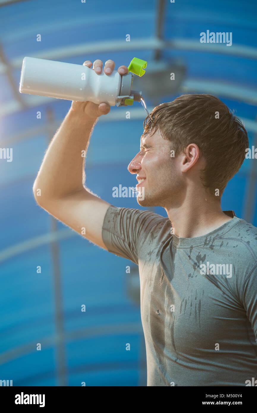 Joven atlético agua potable después de duro entrenamiento Imagen De Stock