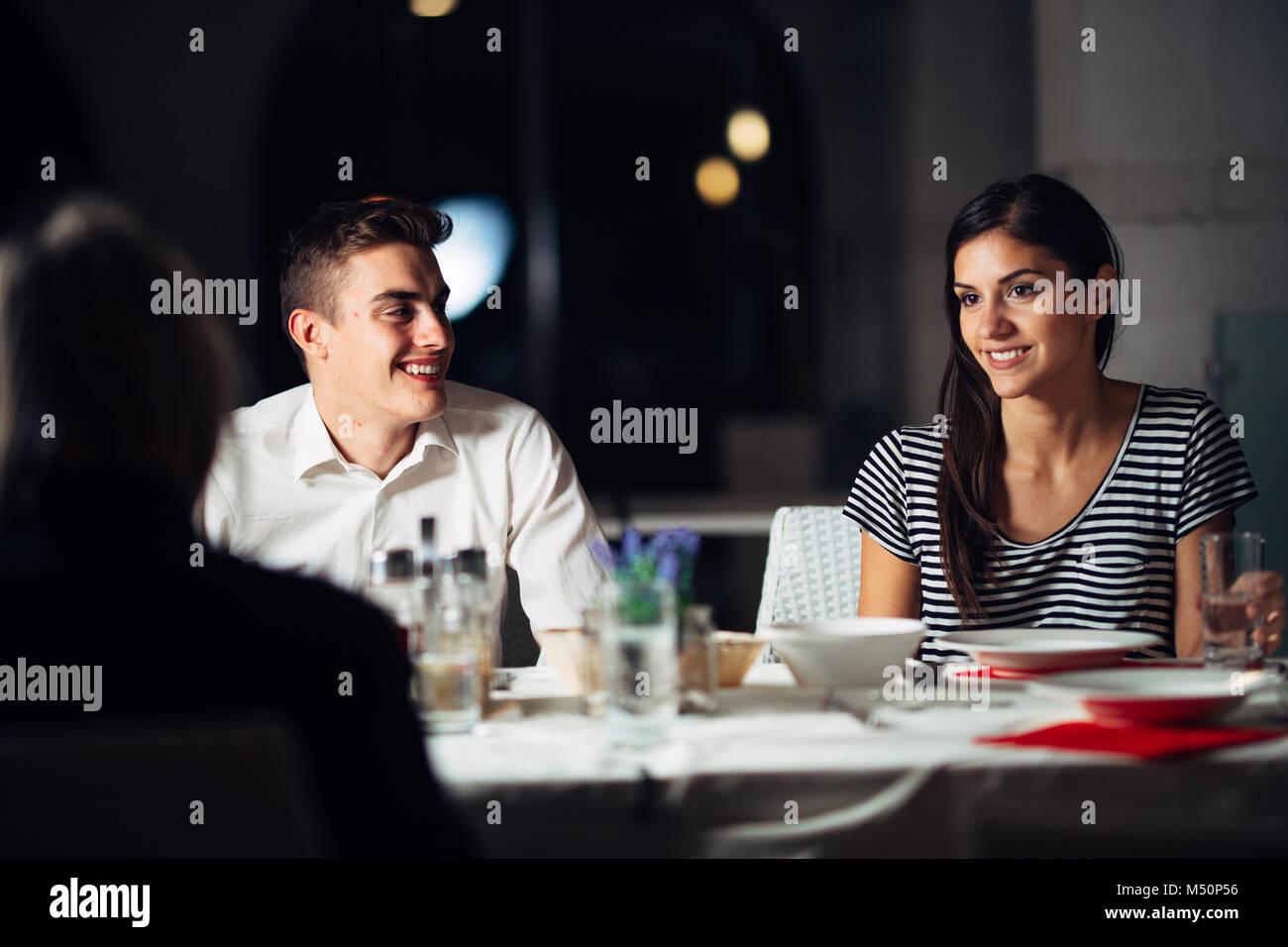 Grupo de amigos tener una cena en un restaurante.Double date.atractivo pueblo de salir por la noche, cena en un Imagen De Stock