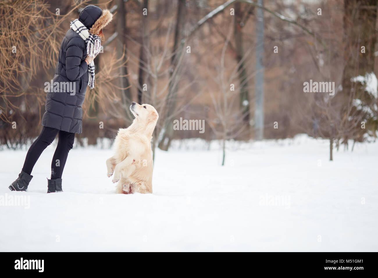 Imagen del joven en Chaqueta negra la formación de perro en el parque de nieve Imagen De Stock