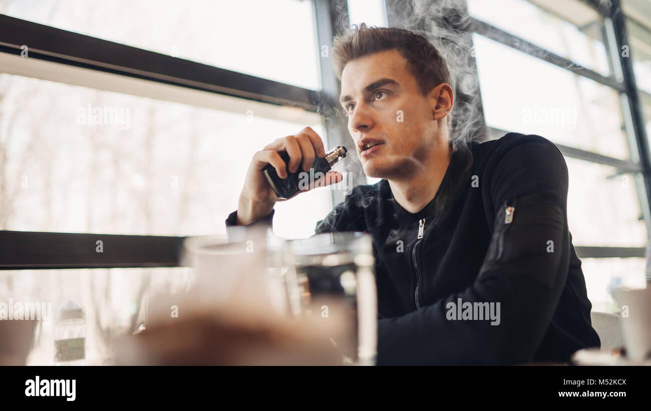 Joven vaping cerrada en el espacio público.Fumar cigarrillo electronico en cafe.La adicción a la nicotina.Forma para dejar de fumar,viejo hábito.Vaping aroma,hombre urbano u Foto de stock