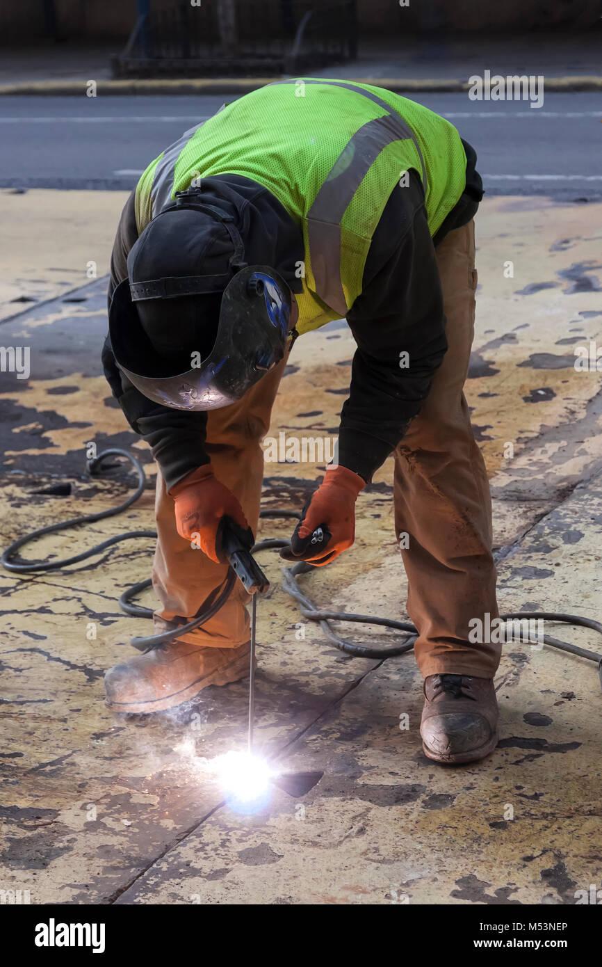 Un trabajador de soldar una placa de acero en una calle de la ciudad de Nueva York. Foto de stock