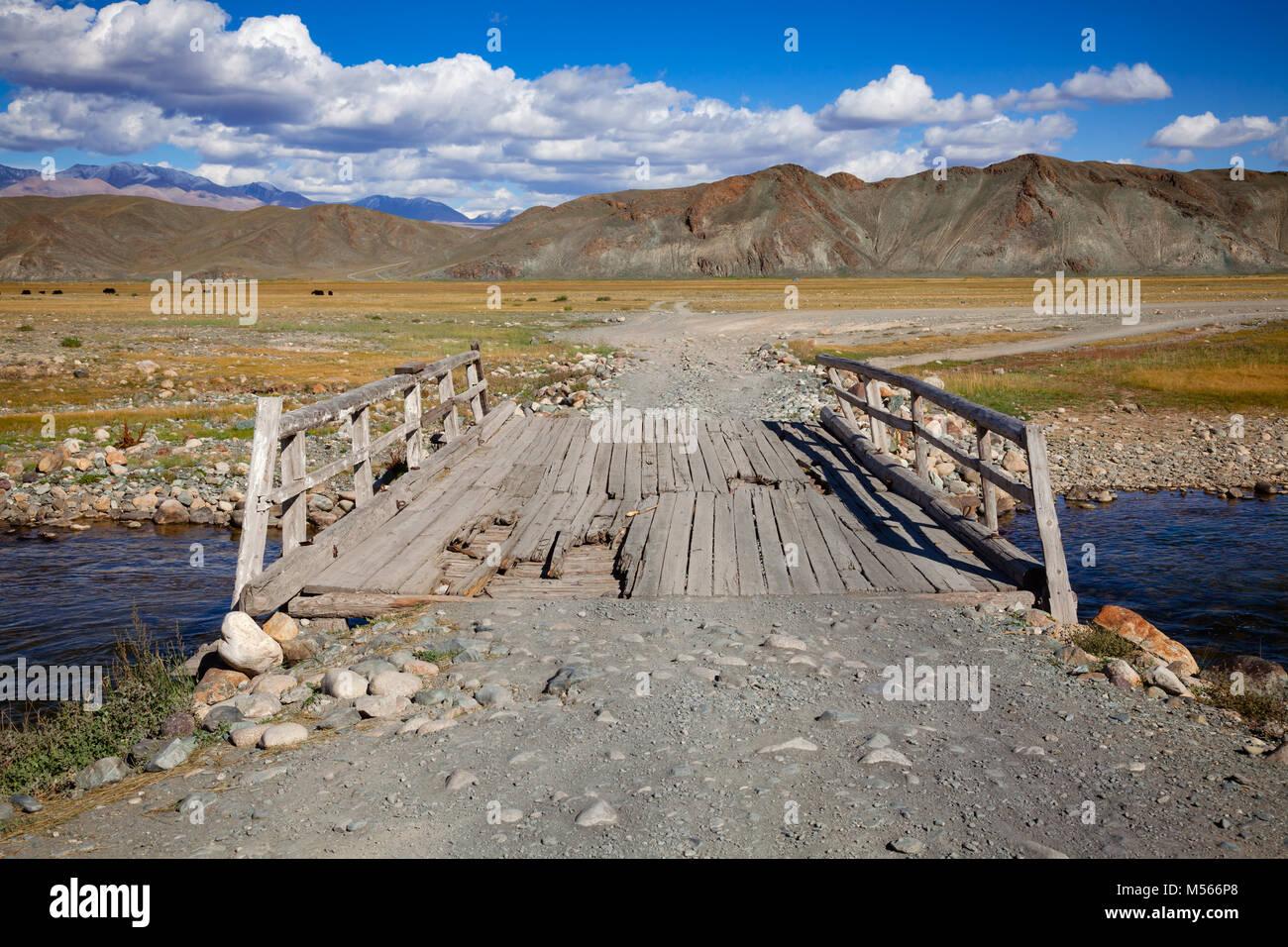 Puente de madera desgastada en una carretera de tierra en las montañas de Altai, Mongolia occidental Foto de stock