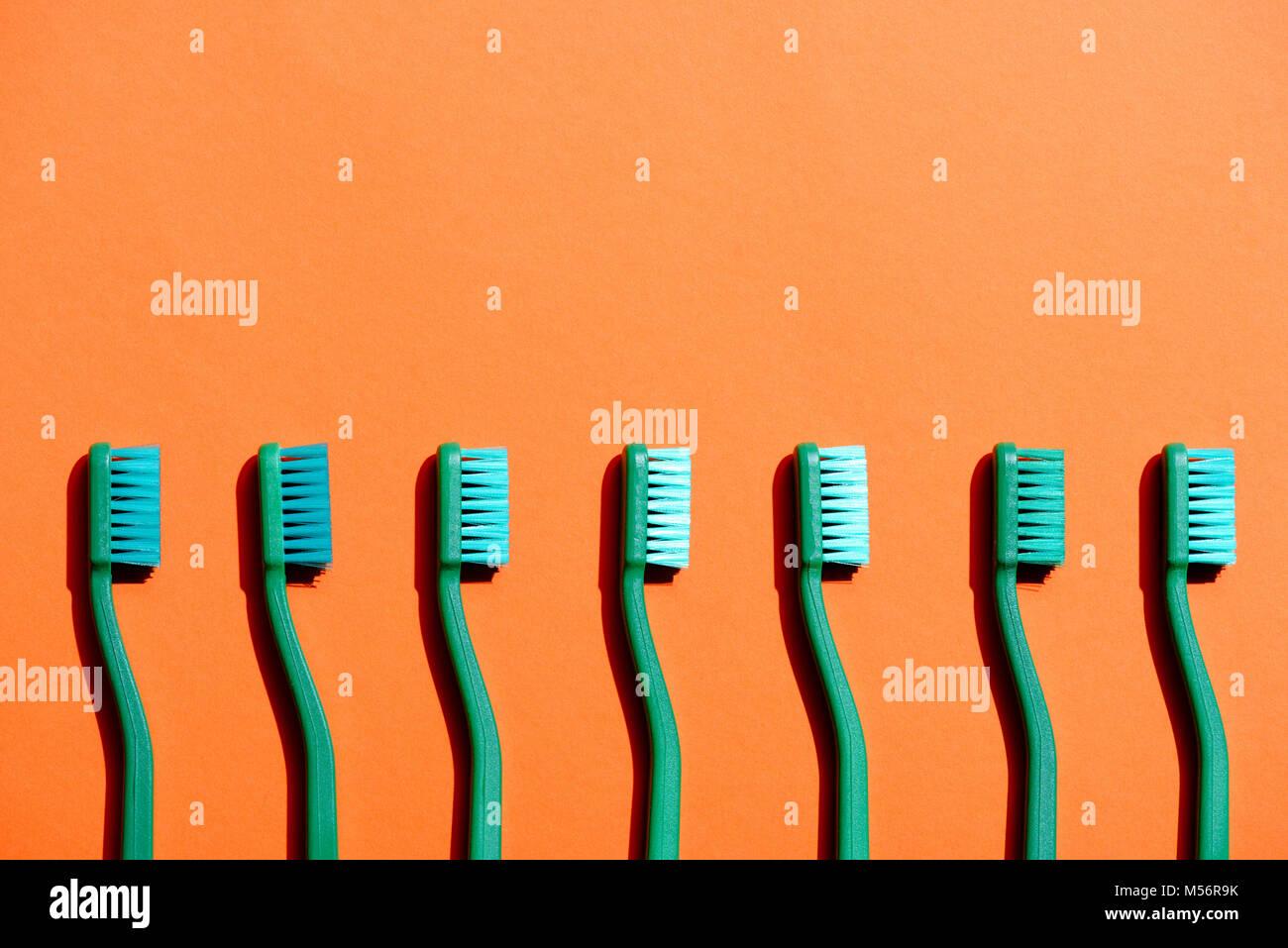 Cepillos de dientes verde en fila, en naranja con espacio de copia Foto de stock