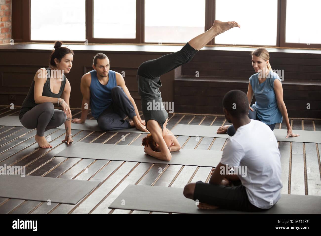 Mujer de pie en la cabeza practicando yoga en la clase de formación en grupo Imagen De Stock