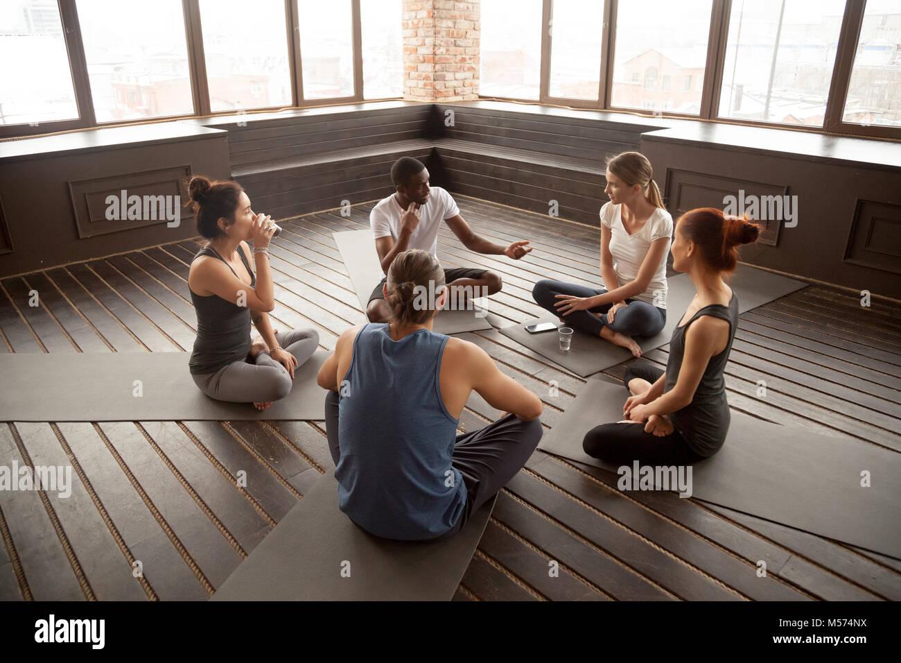 Instructor de yoga americano africano hablando con diversos grupos quedarte sentado Imagen De Stock