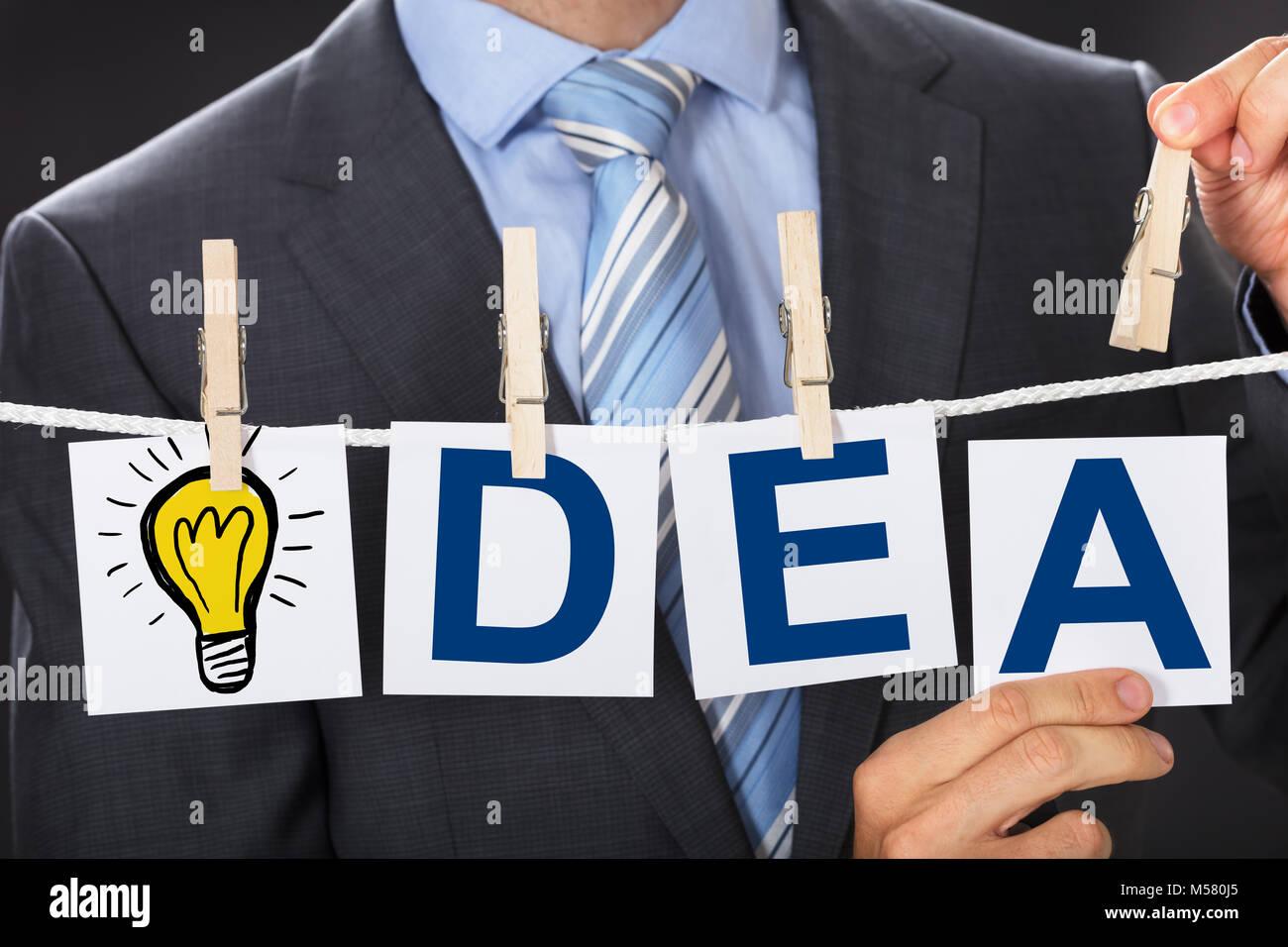 Closeup central del empresario pinning IDEA tarjetas en tendedero Imagen De Stock