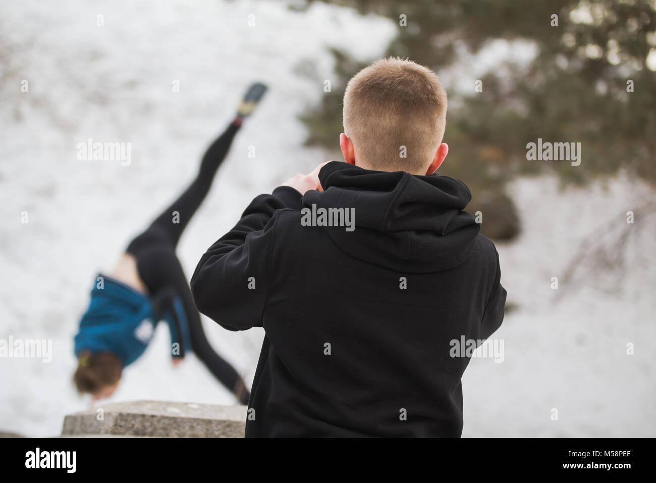 Adolescente chico busca chica Salto acrobático en invierno, el parque de la ciudad - parkour concepto Imagen De Stock