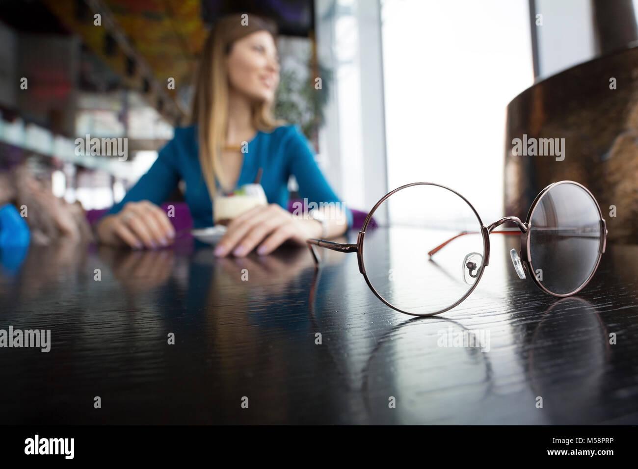 Linda chica sentada en el café y mirando por la ventana Imagen De Stock