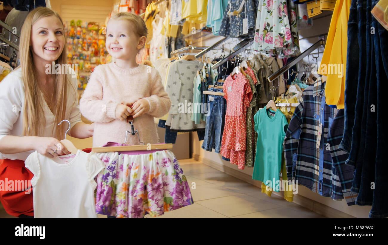 Madre con su pequeña hija en la tienda de ropa para niños Imagen De Stock