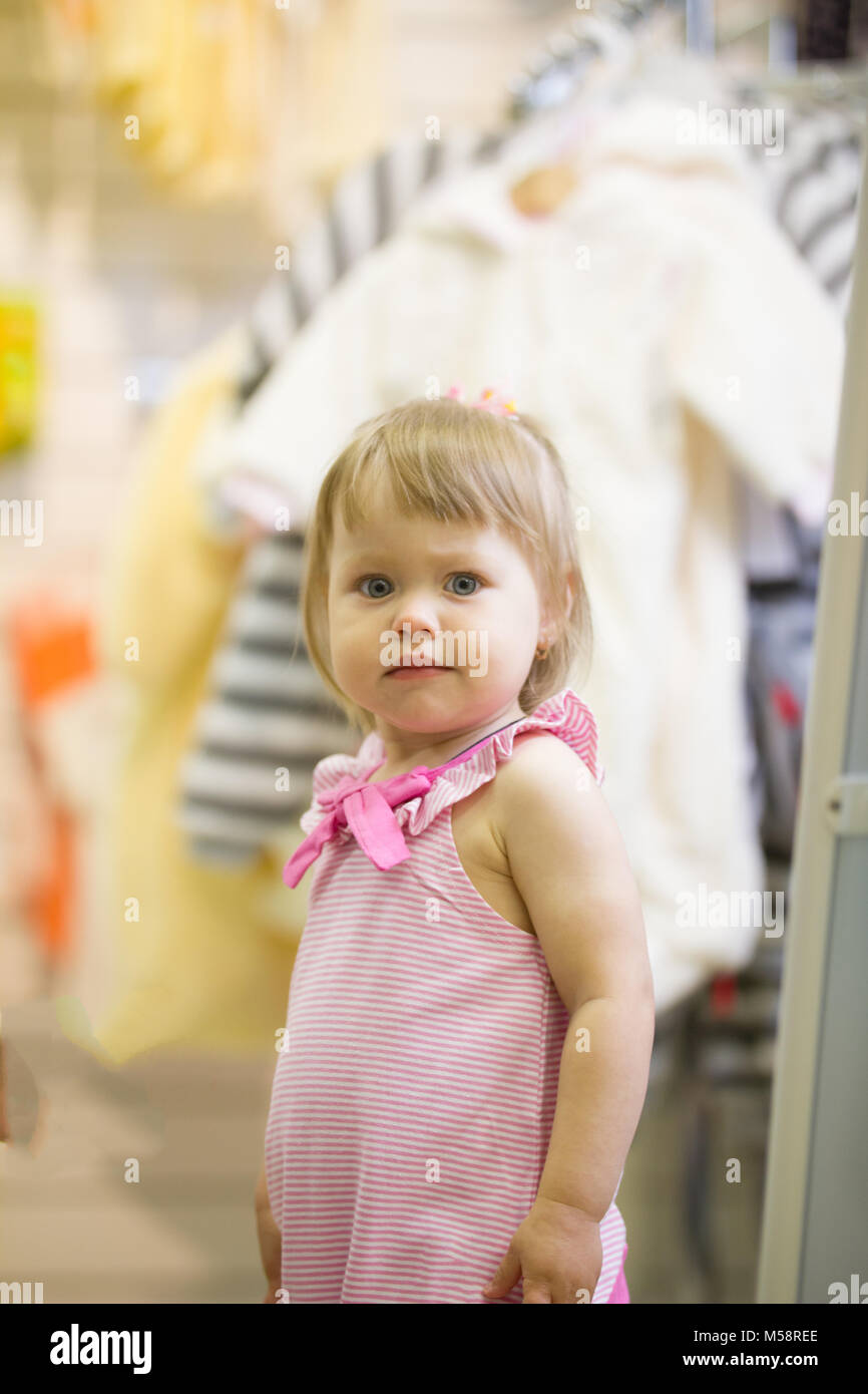 Feliz de niña en la tienda de ropa para niños Imagen De Stock