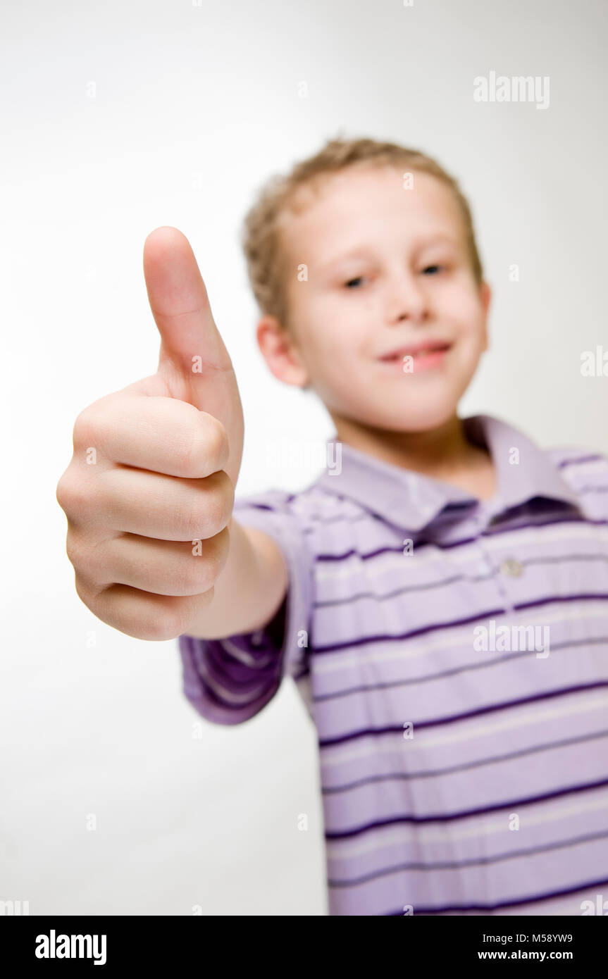 Vista de la parte superior del cuerpo de un niño de siete años contra el fondo blanco con el pulgar apuntando Imagen De Stock