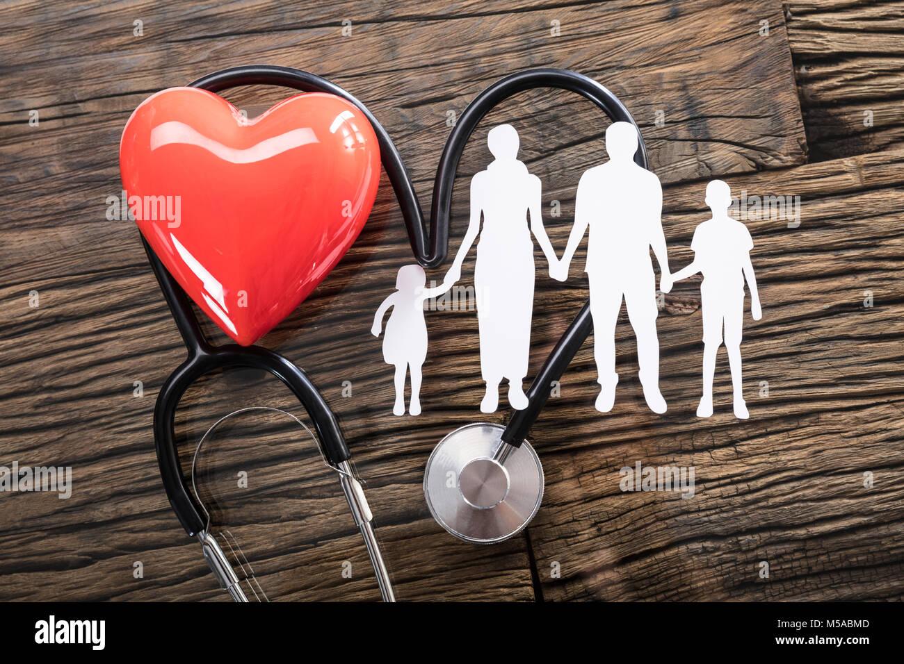 Vista elevada de corte familiar y rojo el corazón con un estetoscopio sobre el escritorio Imagen De Stock
